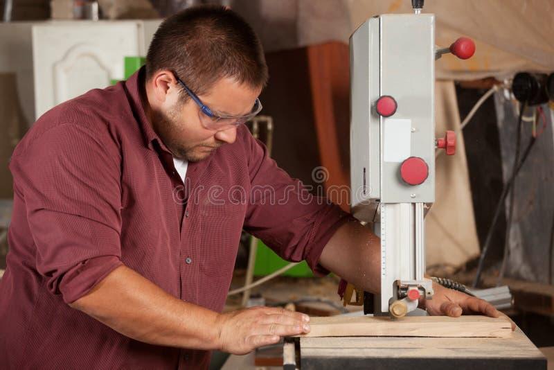 Professionele timmerman die met zaagmachine werken royalty-vrije stock afbeeldingen
