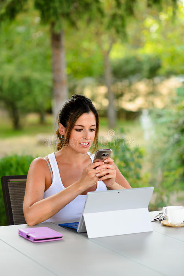 Professionele toevallige vrouw met buiten laptop en smartphone stock foto
