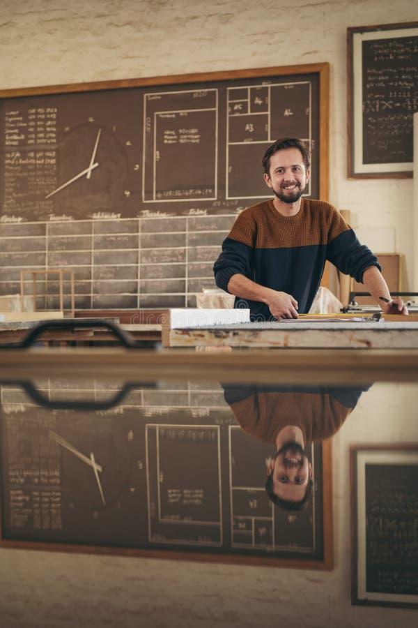 Professionele vakman die terwijl bij het werk in zijn studio glimlachen stock afbeeldingen