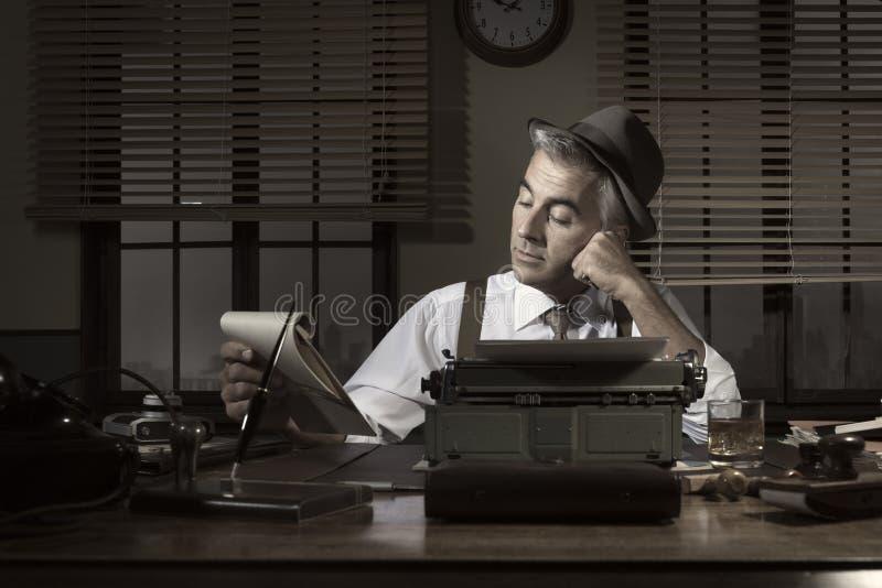 Professionele verslaggever die laat bij nacht werken stock afbeelding