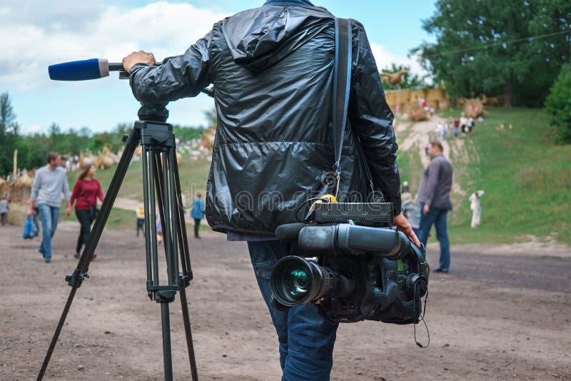 Professionele videoexploitant of videographer status met driepoot en digitale camera stock foto