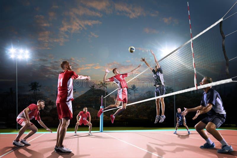 Professionele volleyballspelers in actie betreffende het nachthof royalty-vrije stock fotografie