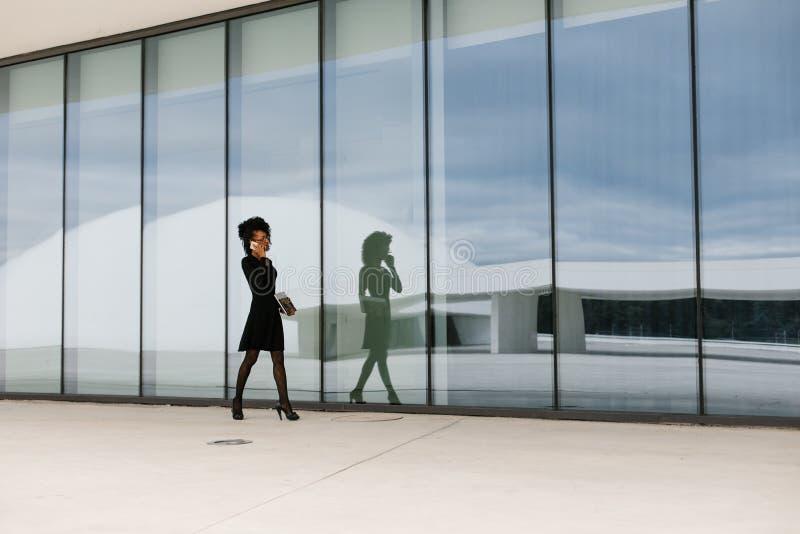 Professionele vrouw die en op cellphone buiten lopen spreken royalty-vrije stock afbeelding
