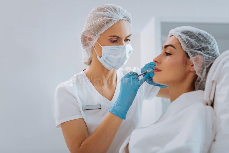 Professionele vrouwelijke cosmetologist die een schoonheidsinjectie doen stock afbeeldingen