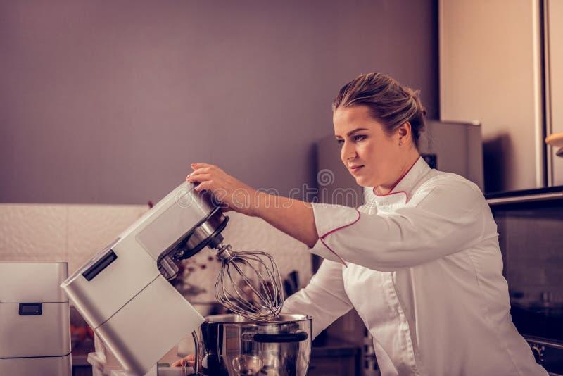 Professionele vrouwelijke gebakjechef-kok die keukenmachine met behulp van stock fotografie