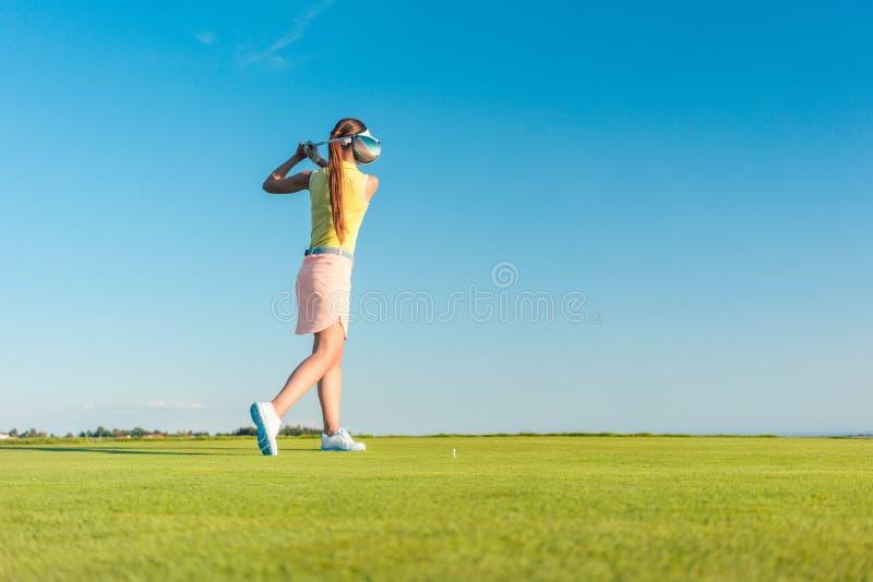 Professionele vrouwelijke golfspeler die terwijl het slingeren van een bestuurder glimlachen royalty-vrije stock afbeelding