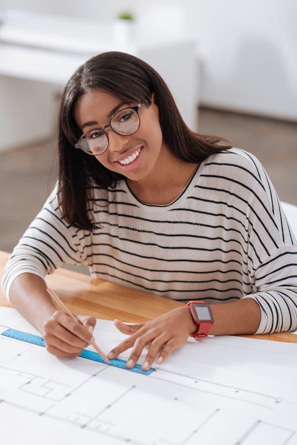 Professionele vrouwelijke ingenieur die tekeningshulpmiddelen met behulp van royalty-vrije stock afbeeldingen