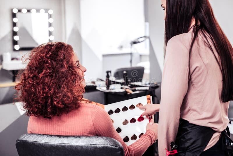 Professionele vrouwelijke kapper die één haarkleur adviseren stock afbeelding