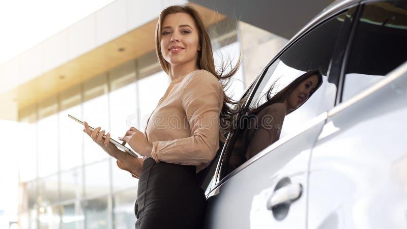 Professionele vrouwelijke manager met tablet die zich dichtbij auto bij de bureaubouw bevinden royalty-vrije stock afbeeldingen