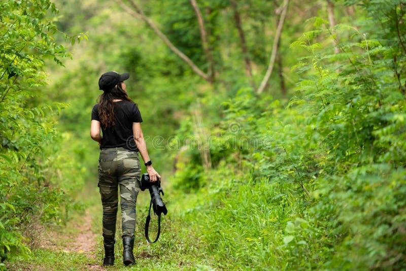 Professionele vrouwenfotograaf die openluchtportretten met eerste lens in de groene bosaard nemen royalty-vrije stock afbeelding
