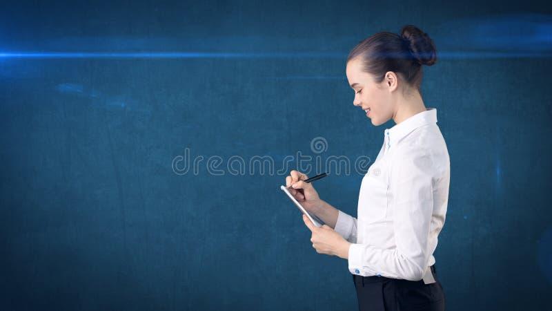 Professionele zekere onderneemster die met broodje in haar die organisator schrijven op studioachtergrond wordt geïsoleerd Bedrij stock afbeeldingen