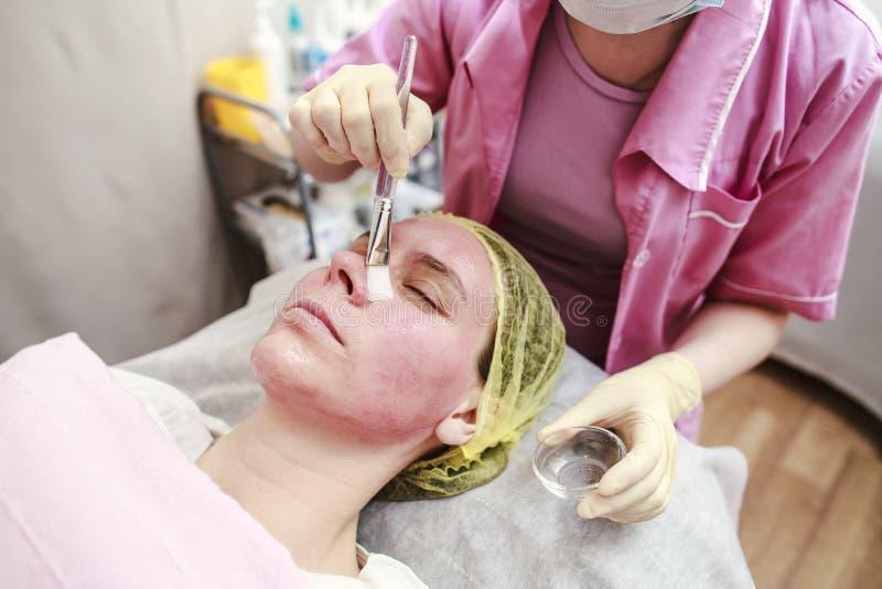 Professionell - kosmetologen sätter på huden för den kemiska peelen arkivbild