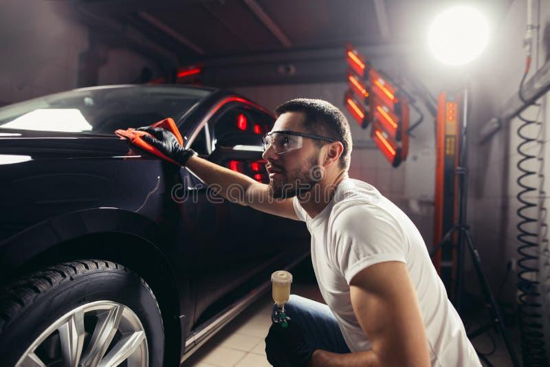 Professionelle Autopflege - der Mann hält das microfiber in der Hand und poliert das Auto lizenzfreies stockfoto