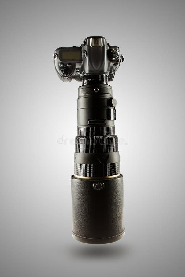 Professionelle digitale Fotokamera mit dem enormen Teleobjektiv lokalisiert auf grauem Steigungshintergrund lizenzfreie stockfotos