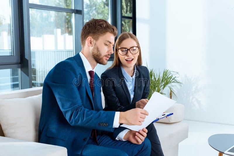 professionelle junge Geschäftsleute, die Papiere besprechen stockbild
