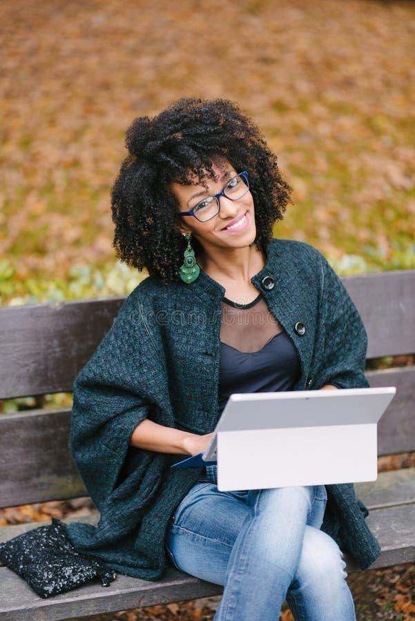 Professionelle schwarze Frau, die mit Laptop draußen im Herbst arbeitet stockfotografie