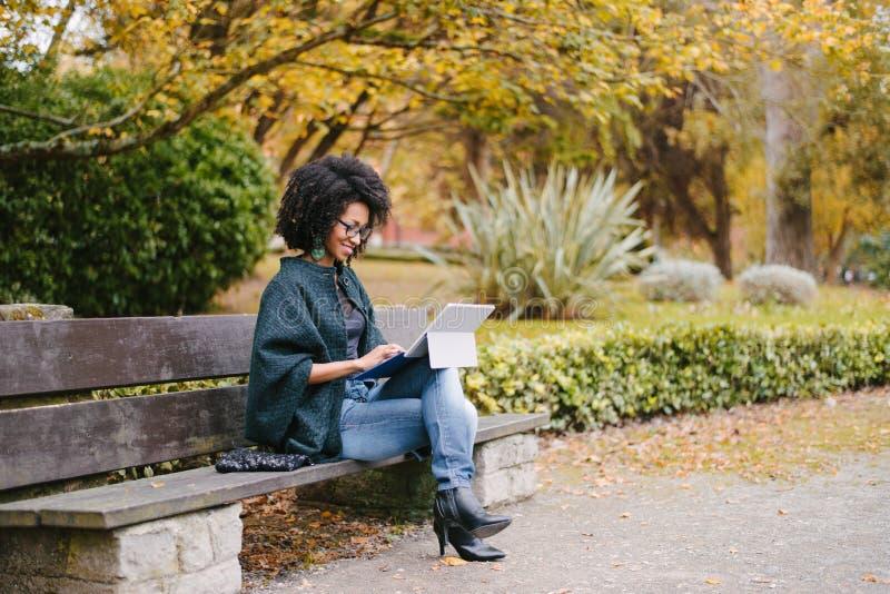 Professionelle schwarze Frau, die mit Laptop draußen im Herbst arbeitet lizenzfreies stockfoto