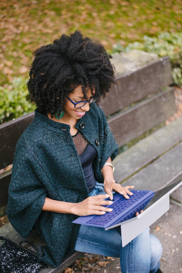 Professionelle schwarze Frau, die mit Laptop draußen im Herbst arbeitet stockbild