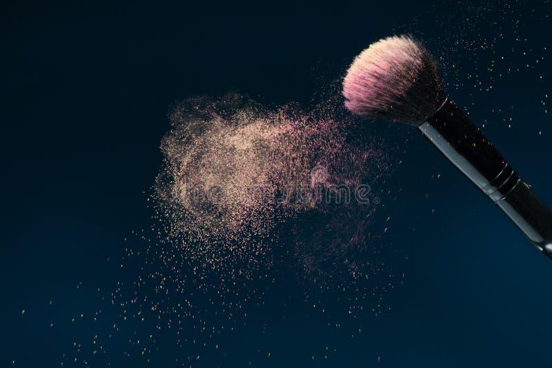 Professionelle schwarze Make-upbürste mit rosa Pulver stockbild