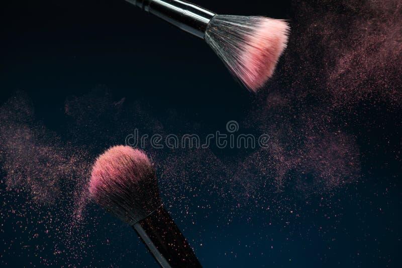 Professionelle schwarze Make-upbürste mit rosa Pulver stockfotografie