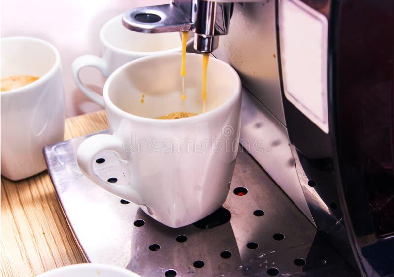 Professionelle silberne Maschine des schwarzen Kaffees mit weißer Schale und strömendem Getränk lizenzfreie stockbilder