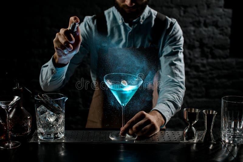 Professioneller Bartender bespritzt mit einem Bitter auf einem blauen alkoholischen Cocktail in einem Martini-Glas mit Spikelett stockfotos