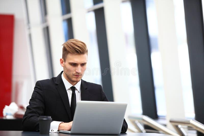 Professioneller hübscher Geschäftsmann unter Verwendung des Laptops am Arbeitsplatz lizenzfreie stockbilder