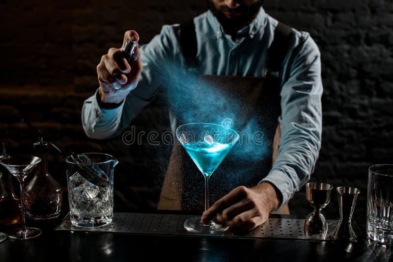 professioneller männlicher Barmann mit einem Bitter auf einem blauen alkoholischen Cocktail in einem Martini-Glas mit einer Dekor stockfotografie