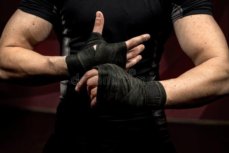 Professioneller männlicher Kämpfer, der für die Ausbildung, seine Hände und Handgelenke wraping sich vorbereitet stockfotografie