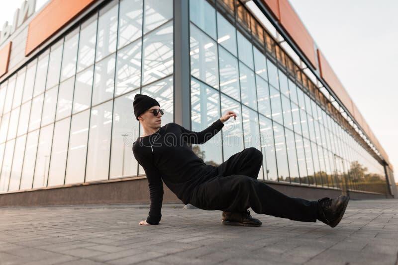 Professioneller Tänzer des jungen Mannes in einer schwarzen modischen Strickmütze in den Jeans in den Turnschuhen in der Sonnenbr lizenzfreie stockfotos