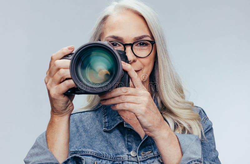 Professioneller weiblicher Fotograf, der ein photoshoot tut stockbilder