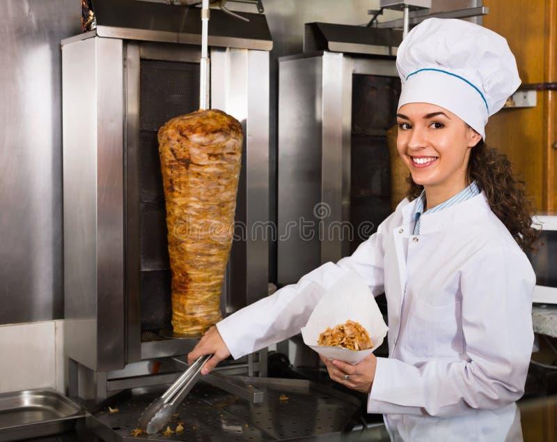 Professioneller weiblicher Koch mit gegrilltem Fleisch auf Spucken für Kebab stockfotografie