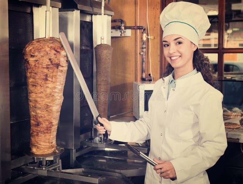 Professioneller weiblicher Koch mit gegrilltem Fleisch auf Spucken für Kebab lizenzfreie stockfotos