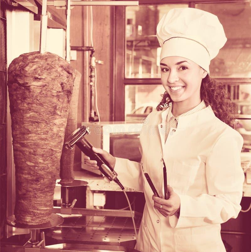 Professioneller weiblicher Koch mit gegrilltem Fleisch auf Spucken für Kebab stockbilder