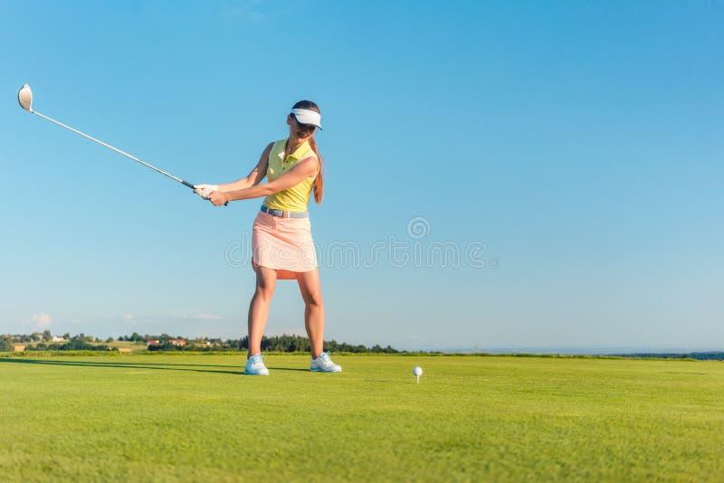 Professioneller weiblicher lächelnder Golfspieler beim Schwingen eines Fahrerclubs lizenzfreie stockfotos