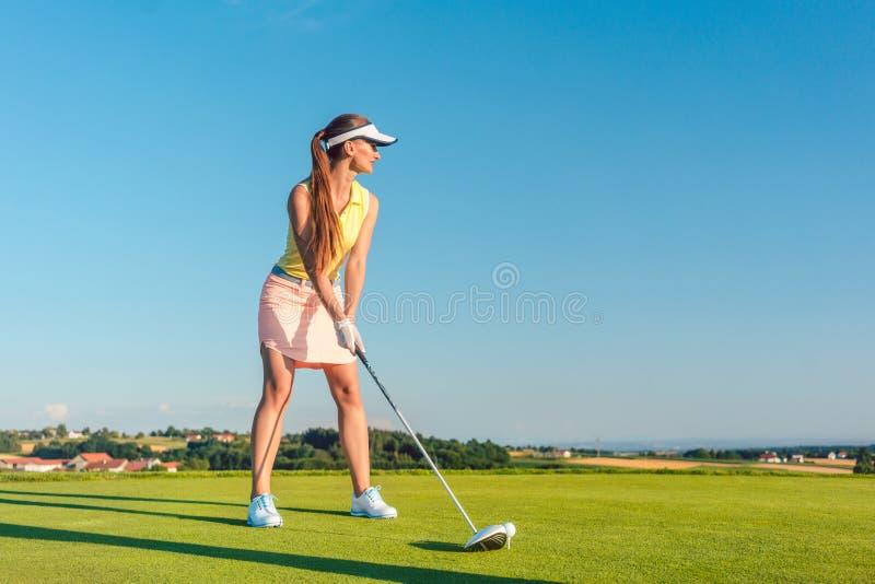 Professioneller weiblicher lächelnder Golfspieler beim Schwingen eines Fahrerclubs lizenzfreies stockfoto