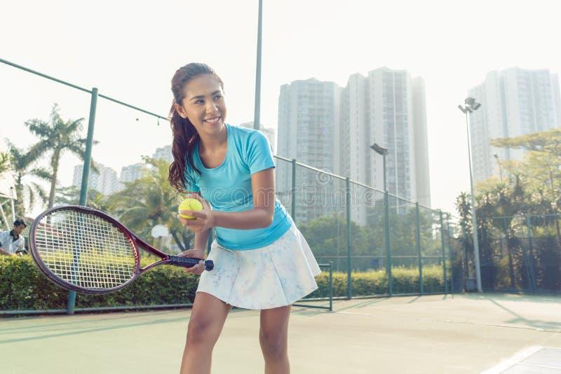Professioneller weiblicher lächelnder Spieler beim Dienen während des Tennismatches lizenzfreie stockbilder