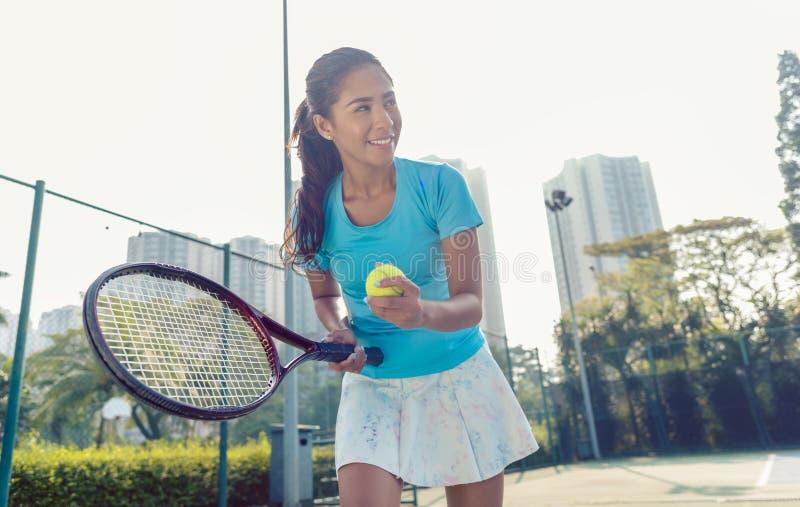 Professioneller weiblicher lächelnder Spieler beim Dienen während des Tennismatches lizenzfreie stockfotografie