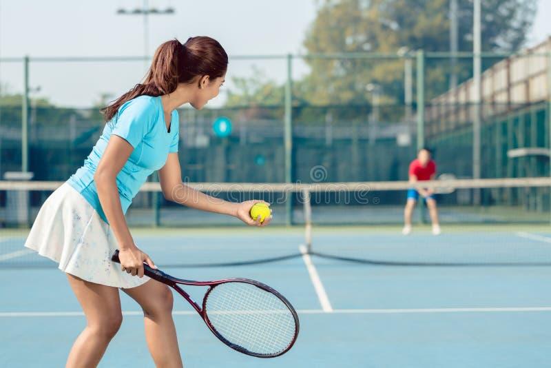 Professioneller weiblicher lächelnder Spieler beim Dienen während des Tennismatches lizenzfreie stockfotos