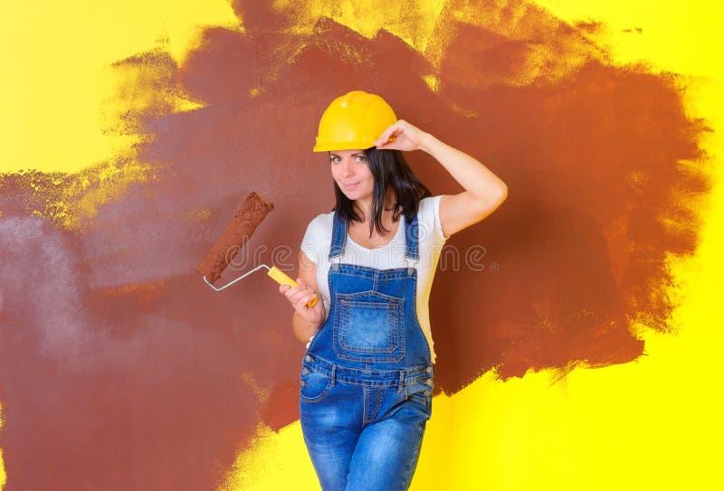 Professioneller weiblicher Maler in einem Bausturzhelm mit einer Farbenrolle stockfotografie