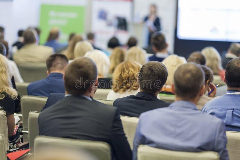 Professioneller weiblicher Wirt, der vor dem breiten Publikum während der Geschäftskonferenz spricht lizenzfreie stockbilder