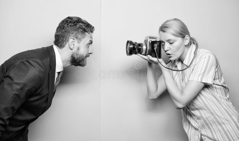 Professionelln som tar bilder Sexig flicka som anv?nder den yrkesm?ssiga kameran ( Manframstickande royaltyfria bilder
