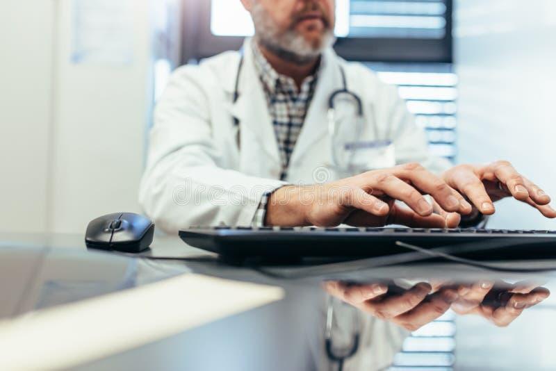 Professionista medico che utilizza la tastiera di computer nella clinica fotografia stock