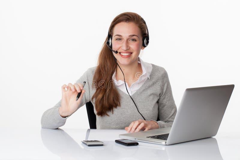 Professionista sorridente 20s con la cuffia avricolare ed il computer in ufficio bianco fotografia stock