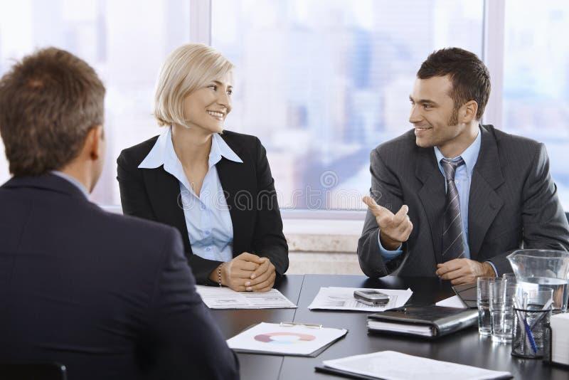 Professionisti sorridenti in ufficio immagine stock