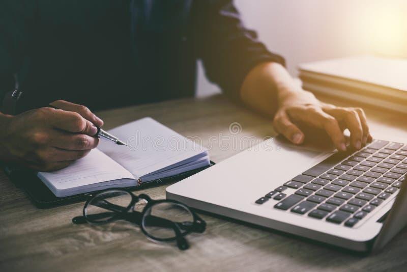 Professionnel au travail, rapport d'écriture d'homme d'affaires et lapto d'utilisation image stock
