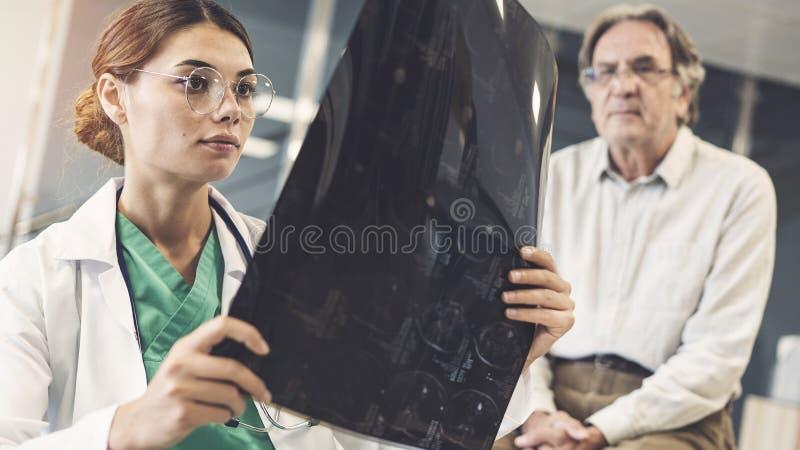 Professionnel de la santé regardant le rayon X images stock