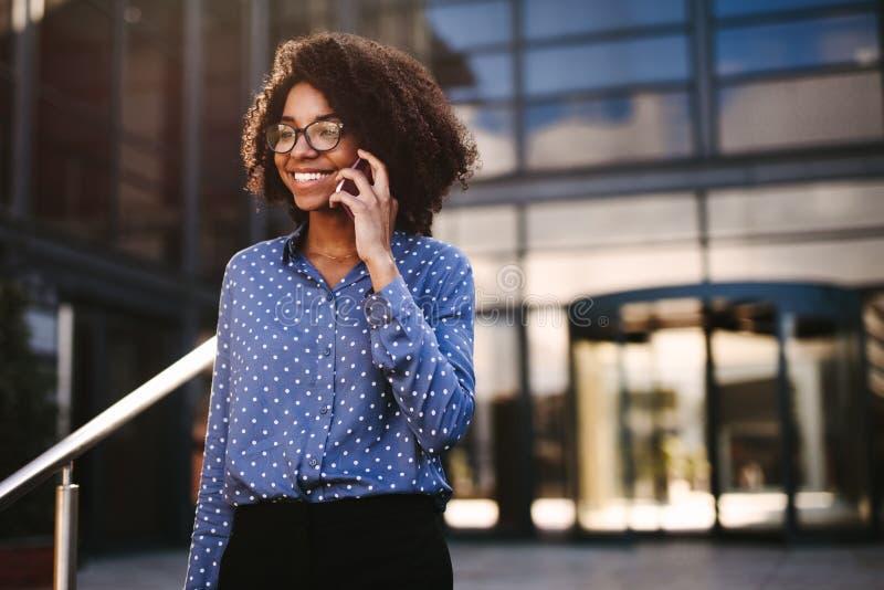 Professionnel féminin d'affaires marchant dehors utilisant le téléphone photo libre de droits