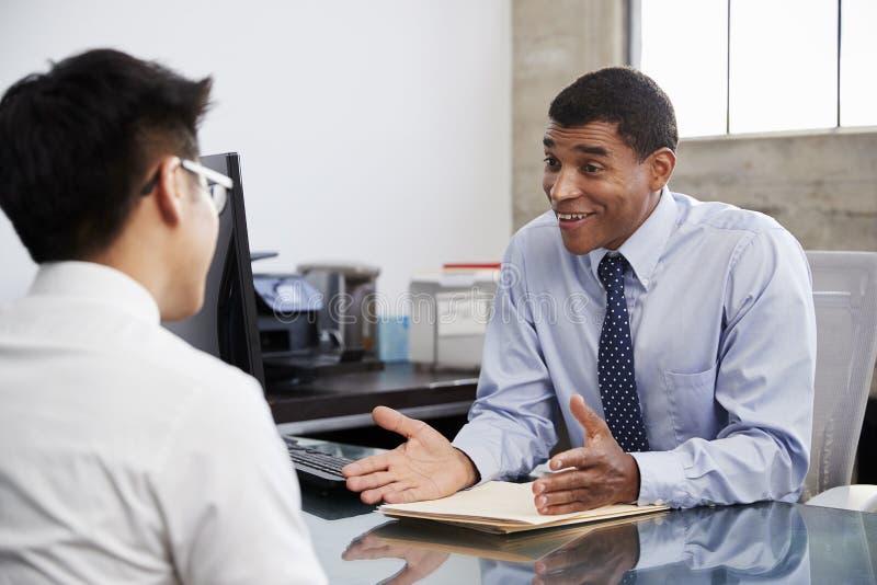 Professionnel masculin de métis lors de la réunion avec le jeune homme asiatique images stock