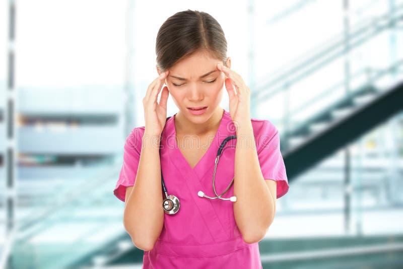 Professionnelle médicale soumise à une contrainte d'infirmière avec le mal de tête photos stock